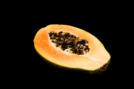 A half of papaya on black