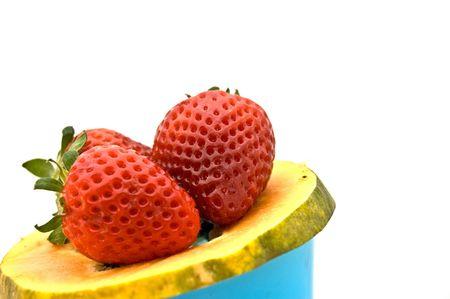 Photo of strawberries on slice of papaya