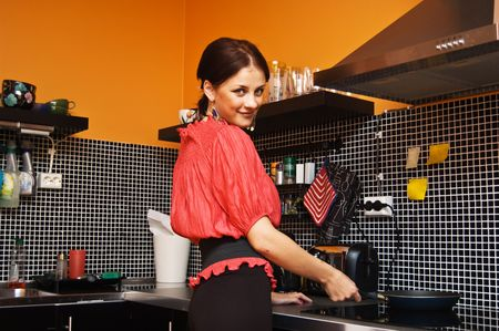 Beautiful nice dressed woman cooking
