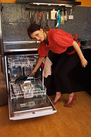 Young woman loading dishwasher on modern kitchen Stock Photo