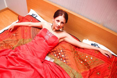 Beautiful woman in red dress lying on the bed Stock Photo - 4788462