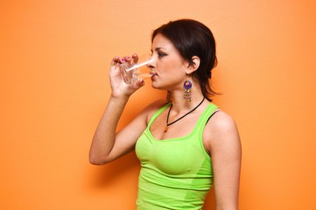 Young sporty woman drinking water