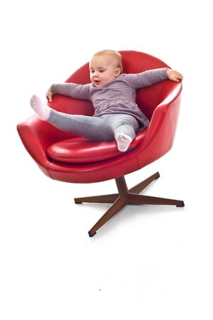 Babygirl on red skin armchair Stock Photo