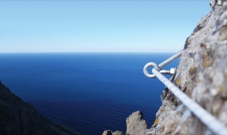 crack climbing: Iron piton in a granite rock with rope Stock Photo