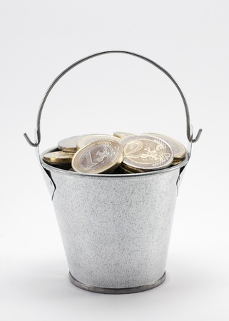 Bucket with coins isolated on white with clipping path photo