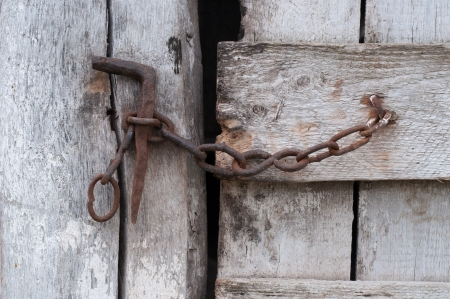 keep gate closed: Chain on an old wooden door