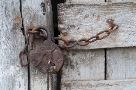 keep gate closed: Lock with a chain on an old wooden door