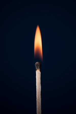 Match burning on a dark background