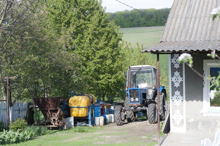 Farm tractor stands in ukrainian village photo
