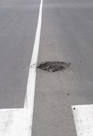 dividing lines: Potholes on a road with white dividing lines