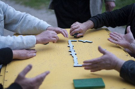 dominoes: Men playing dominoes at table