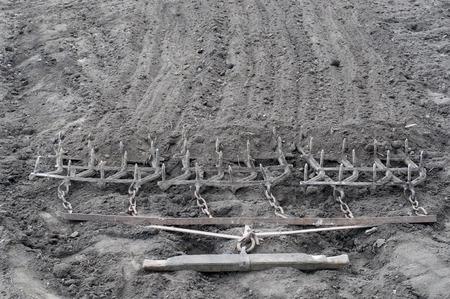 harrow: Harrow. Ancient iron plow on the earth. Old garden tools