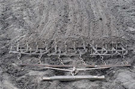Harrow. Ancient iron plow on the earth. Old garden tools
