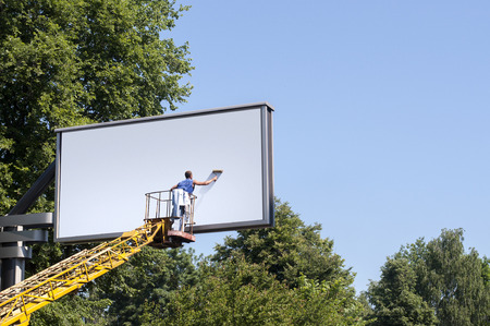 one lane sign: Man putting a new, blank poster to a billboard Stock Photo