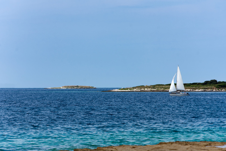 Sailboat glides across the bright blue ocean 스톡 콘텐츠