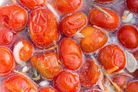 Pickled tomatoes in marinade. closeup.