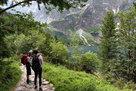 Young man and woman exploring road in the mountain. Tatra National Park, Poland.