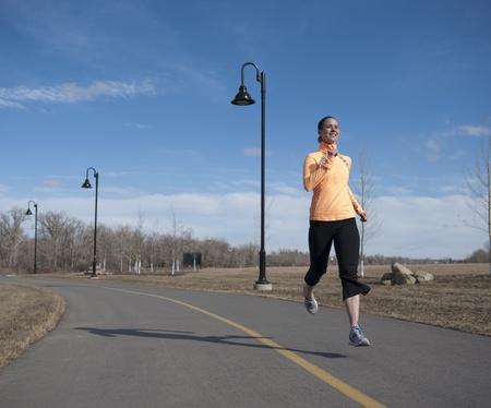 Young woman enjoying a run through an urban park