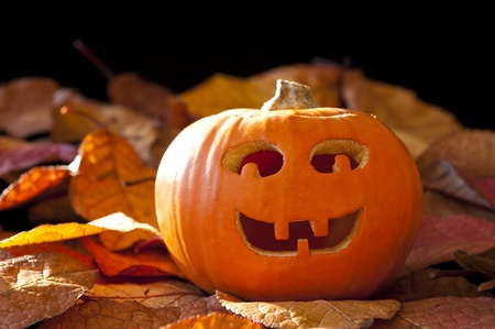 Smiley Jack-o-lantern with colorful autumn leaves Stock Photo