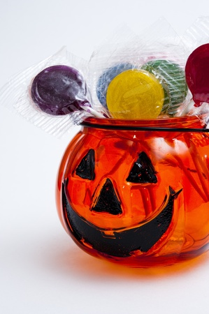 Glass Jack-o-lantern filled with lollipops of assorted colors