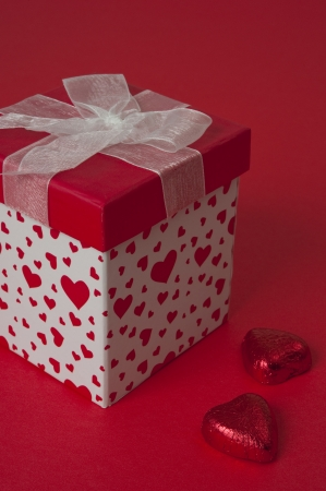Red and white heart gift with heart chocolates on red background photo