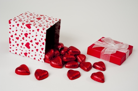Heart Gift box tipped and spilling chocolate hearts Stock Photo