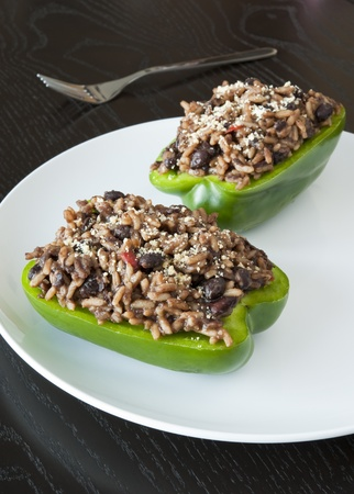Two stuffed green peppers on a dark table Stock Photo