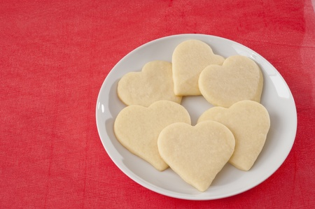 White plate of heart shaped cookies on a red background
