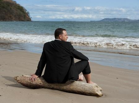 ビーチでのドリフトの木の部分にリラックス ビジネス スーツを着た男