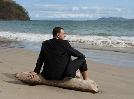 Man in a business suit relaxing on a piece of drift wood at the beach