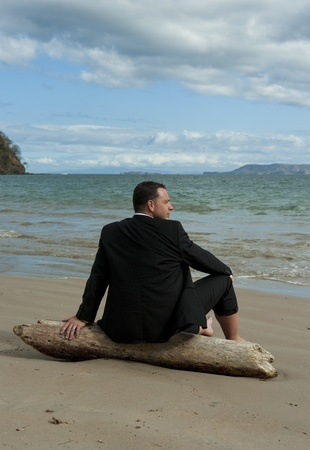 Man in a business suit relaxing on a piece of drift wood at the beach photo