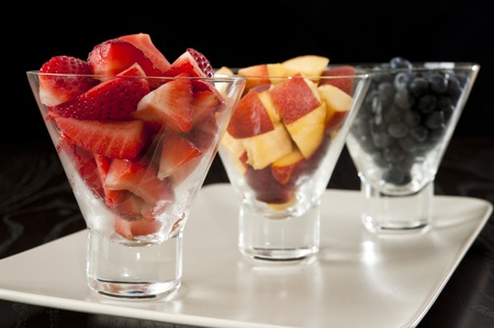 Glass bowls of strawberries, blueberries and nectarines on a white platter
