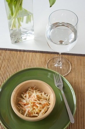 Coleslaw salad in a wooden bowl on a green plate with a water glass