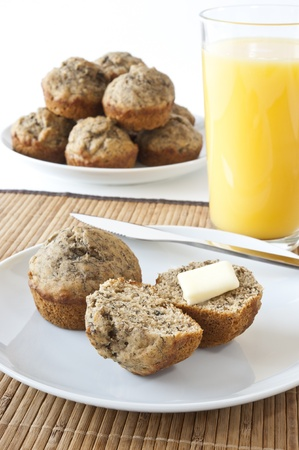 Plate of banana muffins cut and ready to eat with orange juice Stock Photo