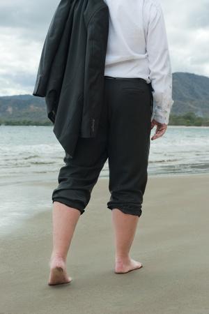 Businessman walking barefoot on a beach Reklamní fotografie