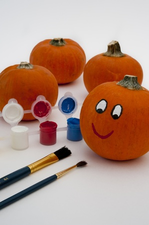 Paints and paintbrushes with a pumkin decorated with a happy face