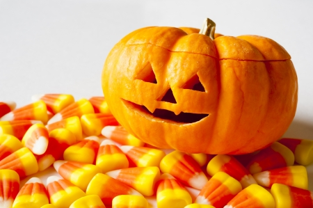 Smiling jack-o-lantern with candy corns on a white background Stock Photo