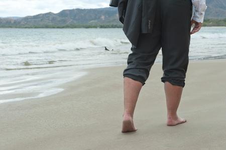 Businessman walking barefoot on a beach photo