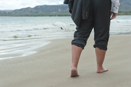 Businessman walking barefoot on a beach photo