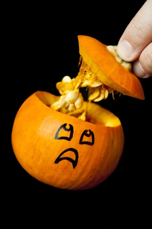 Pumpkin with frightened expression watching his lid and seeds come out Stock Photo - 9543703
