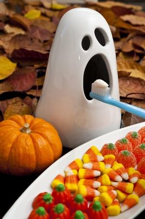 ハロウィーンのキャンディを得る彼の歯はブラシとゴーストします。 写真素材