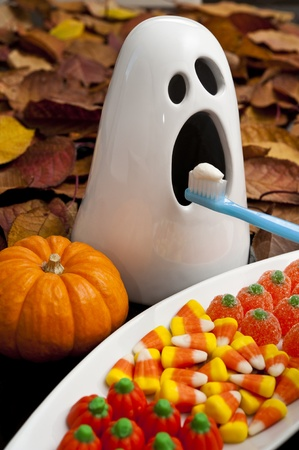 Ghost with Halloween candy getting his teeth brushed photo