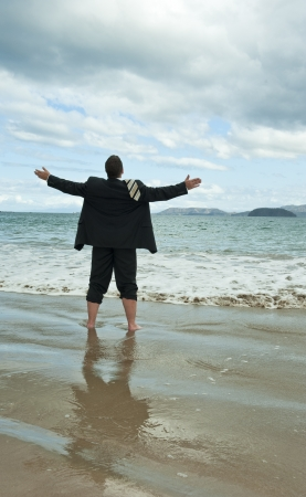 upraised: Businessman standing on the beach with his arms upraised to the sky