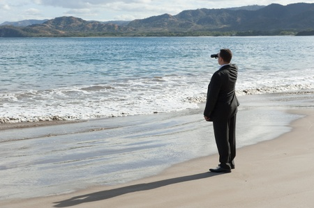 ビジネスの男性、双眼鏡を使って、海を見渡すビーチ