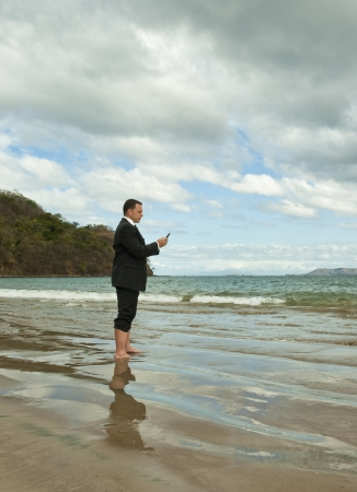 Businessman standing barefoot on a beach texting photo