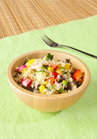 Quinoa salad with colorful vegetables in a wooden bowl photo
