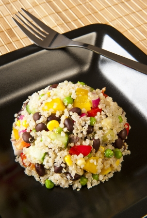 Quinoa salad with colorful vegetables on a black plate photo