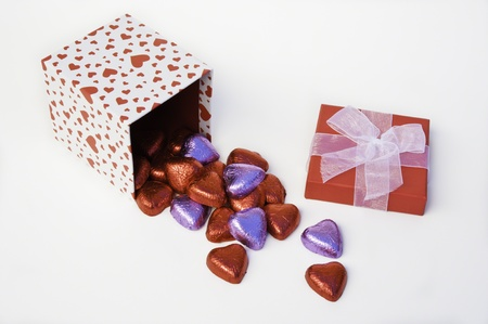 Heart gift box on side spilling red and purple wrapped chocolate hearts photo