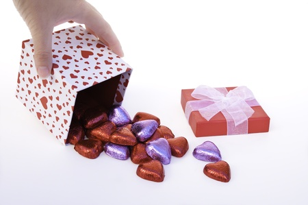 pours: Hand pours red and purple wrapped heart chocolates out of a heart gift box Stock Photo