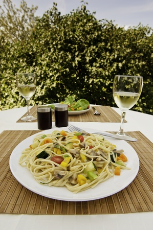 Table set for two with a fresh green salad and  a plate of linguini with colorful vegetables